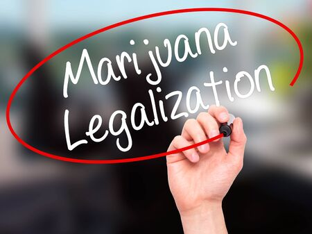 oppose: Man Hand writing Marijuana Legalization with black marker on visual screen. Isolated on office. Live, technology, internet concept. Stock Photo