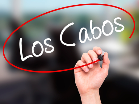 los cabos: Man Hand writing Los Cabos with black marker on visual screen. Isolated on office. Business, technology, internet concept. Stock Photo