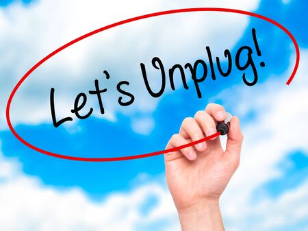 unplug: Man Hand writing Lets Unplug! with black marker on visual screen. Isolated on sky. Business, technology, internet concept. Stock Photo Stock Photo