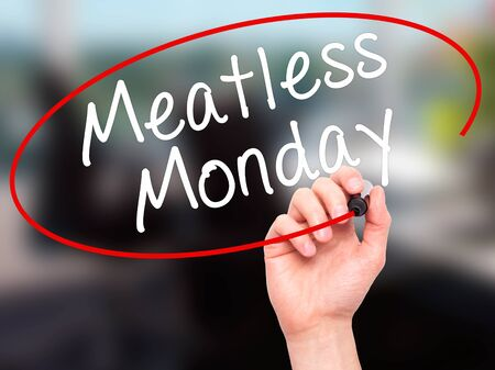 meatless: Man Hand writing Meatless Monday with black marker on visual screen. Isolated on office. Life, technology, internet concept. Stock Image Stock Photo