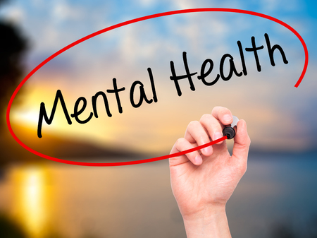 meditation help: Man Hand writing Mental Health with black marker on visual screen. Isolated on nature. Business, technology, internet concept. Stock Photo