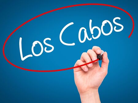 los cabos: Man Hand writing Los Cabos with black marker on visual screen. Isolated on blue. Business, technology, internet concept. Stock Photo