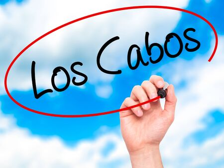 los cabos: Man Hand writing Los Cabos with black marker on visual screen. Isolated on sky. Business, technology, internet concept. Stock Photo Stock Photo