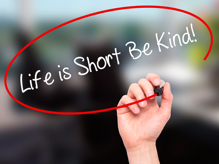 helpfulness: Man Hand writing Life is Short Be Kind! with black marker on visual screen. Isolated on office. Business, technology, internet concept. Stock Photo