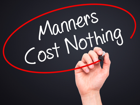 bad manners: Man Hand writing Manners Cost Nothing with black marker on visual screen. Isolated on black. Business, technology, internet concept. Stock Photo
