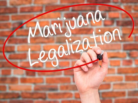 legislators: Man Hand writing Marijuana Legalization with black marker on visual screen. Isolated on bricks. Live, technology, internet concept. Stock Photo