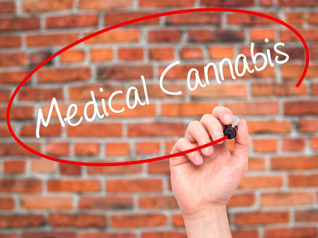 legislators: Man Hand writing Medical Cannabis with black marker on visual screen. Isolated on background. Business, technology, internet concept. Stock Photo