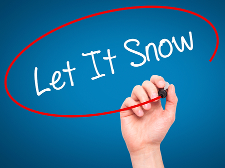 december 25th: Man Hand writing Let It Snow with black marker on visual screen. Isolated on blue. Business, technology, internet concept. Stock Photo