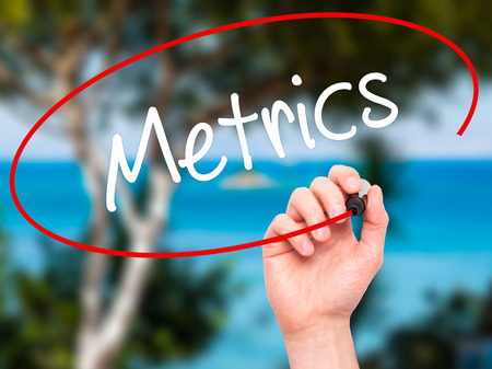 metrics: Man Hand writing  Metrics  with black marker on visual screen. Isolated on background. Business, technology, internet concept. Stock Photo