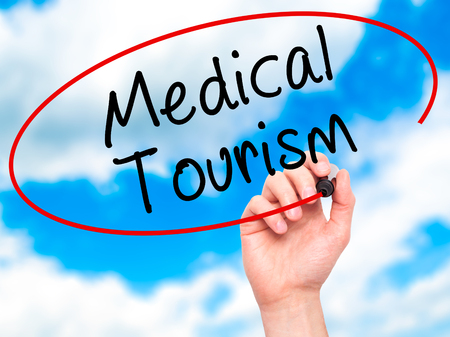 health care fees: Man Hand writing Medical Tourism with black marker on visual screen. Isolated on sky. Business, technology, internet concept. Stock Photo