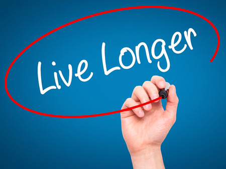longer: Man Hand writing Live Longer with black marker on visual screen. Isolated on blue. Business, technology, internet concept. Stock Photo Stock Photo