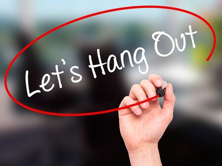 Man Hand writing Lets Hang Out with black marker on visual screen. Isolated on background. Business, technology, internet concept. Stock Photo