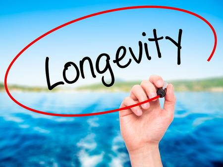 longevity medicine: Man Hand writing Longevity  with black marker on visual screen. Isolated on nature. Business, technology, internet concept. Stock Photo Stock Photo