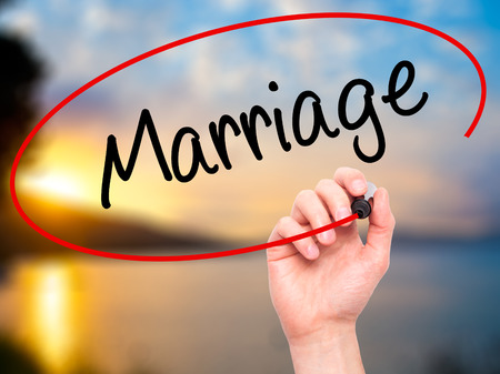 severance: Man Hand writing Marriage with black marker on visual screen. Isolated on nature. Business, technology, internet concept. Stock Photo
