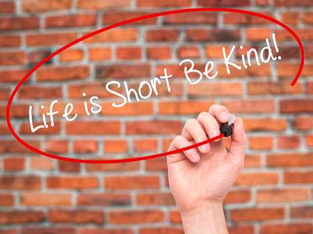 helpfulness: Man Hand writing Life is Short Be Kind! with black marker on visual screen. Isolated on bricks. Business, technology, internet concept. Stock Photo
