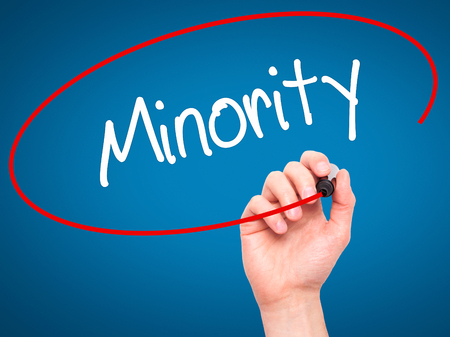 minority: Man Hand writing Minority with black marker on visual screen. Isolated on blue. Business, technology, internet concept. Stock Photo