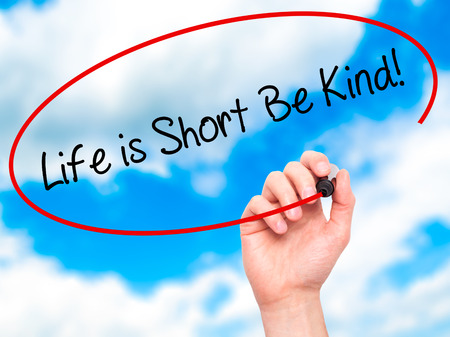 likable: Man Hand writing Life is Short Be Kind! with black marker on visual screen. Isolated on sky. Business, technology, internet concept. Stock Photo Stock Photo