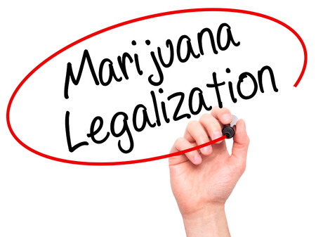 legislators: Man Hand writing Marijuana Legalization with black marker on visual screen. Isolated on white. Live, technology, internet concept. Stock Photo Stock Photo
