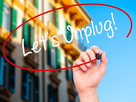 unplug: Man Hand writing Lets Unplug! with black marker on visual screen. Isolated on city. Business, technology, internet concept. Stock Photo