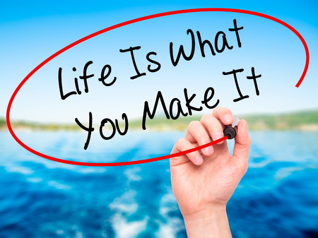 street wise: Man Hand writing Life Is What You Make It with black marker on visual screen. Isolated on background. Business, technology, internet concept. Stock Photo Stock Photo