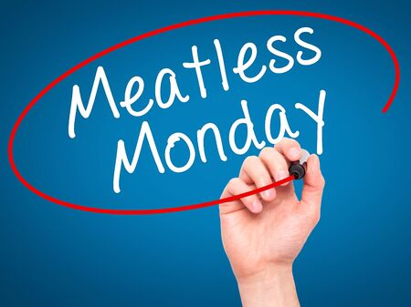 meatless: Man Hand writing Meatless Monday with black marker on visual screen. Isolated on blue. Life, technology, internet concept. Stock Image