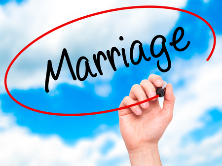 severance: Man Hand writing Marriage with black marker on visual screen. Isolated on sky. Business, technology, internet concept. Stock Photo Stock Photo