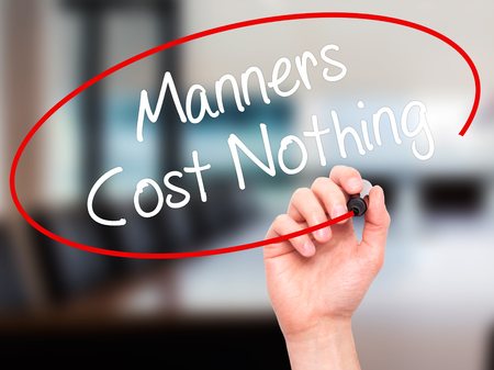believable: Man Hand writing Manners Cost Nothing with black marker on visual screen. Isolated on office. Business, technology, internet concept. Stock Photo