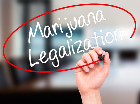 legislators: Man Hand writing Marijuana Legalization with black marker on visual screen. Isolated on office. Live, technology, internet concept. Stock Photo