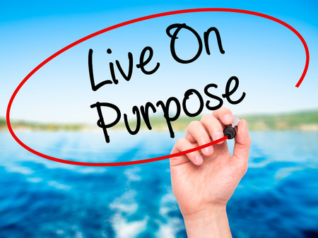 commitment committed: Man Hand writing Live On Purpose  with black marker on visual screen. Isolated on nature. Business, technology, internet concept. Stock Photo