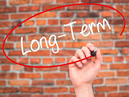 Man Hand writing Long-Term with black marker on visual screen. Isolated on bricks. Business, technology, internet concept. Stock Photo Stock Photo