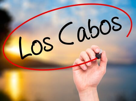 los cabos: Man Hand writing Los Cabos with black marker on visual screen. Isolated on nature. Business, technology, internet concept. Stock Photo