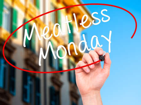 meatless: Man Hand writing Meatless Monday with black marker on visual screen. Isolated on city. Life, technology, internet concept. Stock Image Stock Photo