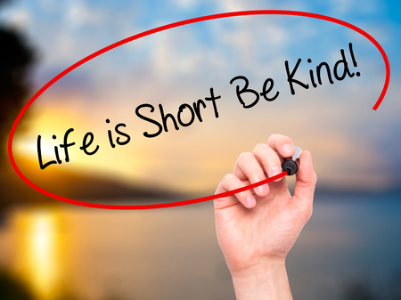 Man Hand writing Life is Short Be Kind! with black marker on visual screen. Isolated on nature. Business, technology, internet concept. Stock Photo