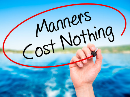 manners: Man Hand writing Manners Cost Nothing with black marker on visual screen. Isolated on nature. Business, technology, internet concept. Stock Photo