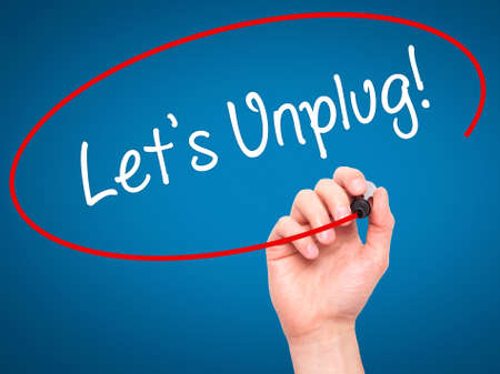 unplug: Man Hand writing Lets Unplug! with black marker on visual screen. Isolated on blue. Business, technology, internet concept. Stock Photo