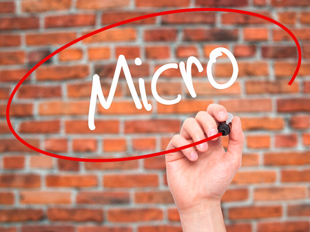 nanotech: Man Hand writing Micro with black marker on visual screen. Isolated on background. Business, technology, internet concept. Stock Photo