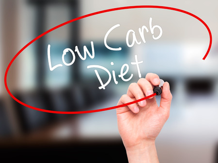low carb diet: Man Hand writing Low Carb Diet with black marker on visual screen. Isolated on office. Business, technology, internet concept. Stock Photo Stock Photo