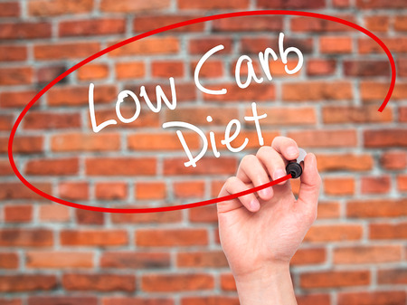 low carb diet: Man Hand writing Low Carb Diet with black marker on visual screen. Isolated on bricks. Business, technology, internet concept. Stock Photo Stock Photo