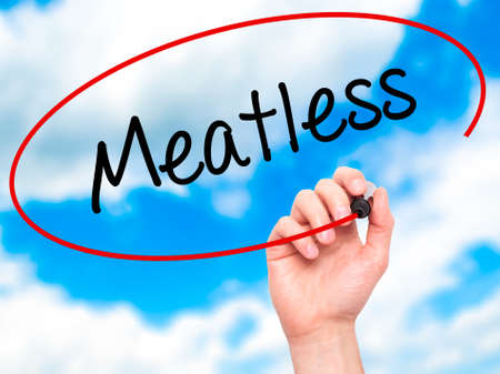 meatless: Man Hand writing Meatless  with black marker on visual screen. Isolated on sky. Business, technology, internet concept. Stock Photo