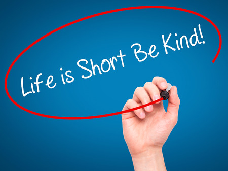 helpfulness: Man Hand writing Life is Short Be Kind! with black marker on visual screen. Isolated on blue. Business, technology, internet concept. Stock Photo