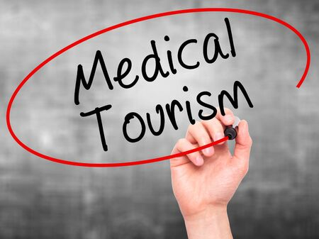 health care fees: Man Hand writing Medical Tourism with black marker on visual screen. Isolated on grey. Business, technology, internet concept. Stock Photo Stock Photo