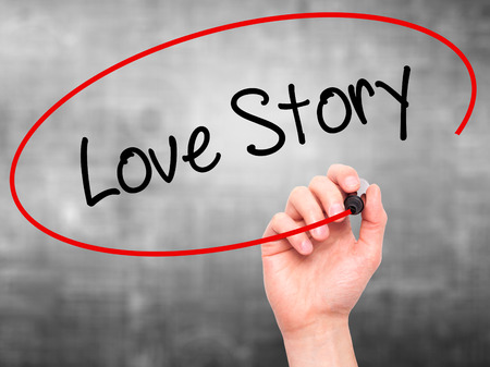 photo story: Man Hand writing Love Story with black marker on visual screen. Isolated on grey. Business, technology, internet concept. Stock Photo Stock Photo