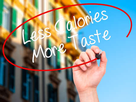 tast: Man Hand writing Less Calories More Taste with black marker on visual screen. Isolated on background. Business, technology, internet concept. Stock Photo