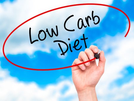 vegetable carbon: Man Hand writing Low Carb Diet with black marker on visual screen. Isolated on sky. Business, technology, internet concept. Stock Photo