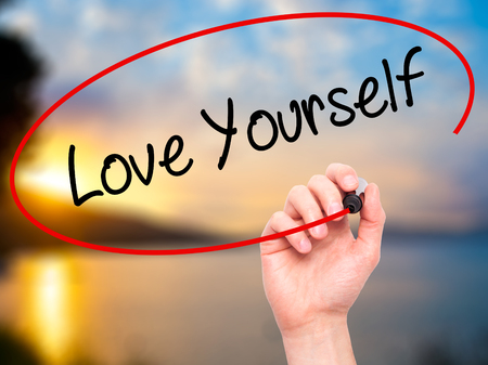 egoistic: Man Hand writing Love Yourself with black marker on visual screen. Isolated on nature. Business, technology, internet concept. Stock Photo