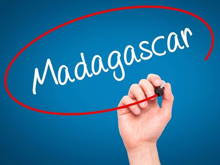fort dauphin: Man Hand writing Madagascar with black marker on visual screen. Isolated on blue. Business, technology, internet concept. Stock Photo