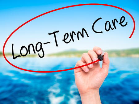 longterm: Man Hand writing Long-Term Care with black marker on visual screen. Isolated on nature. Business, technology, internet concept. Stock Photo