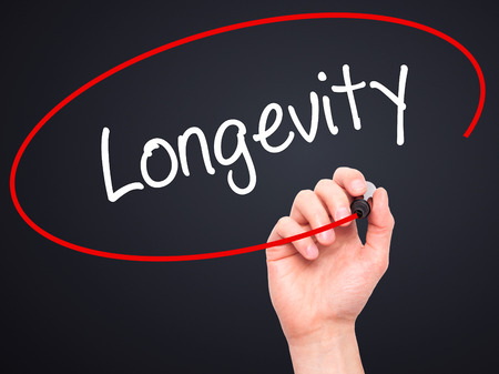 expectancy: Man Hand writing Longevity  with black marker on visual screen. Isolated on black. Business, technology, internet concept. Stock Photo