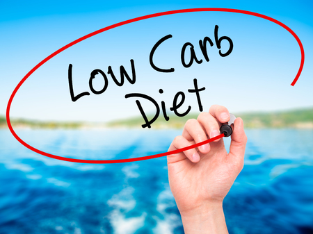 low carb diet: Man Hand writing Low Carb Diet with black marker on visual screen. Isolated on nature. Business, technology, internet concept. Stock Photo