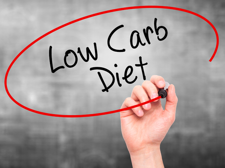 low carb diet: Man Hand writing Low Carb Diet with black marker on visual screen. Isolated on grey. Business, technology, internet concept. Stock Photo
